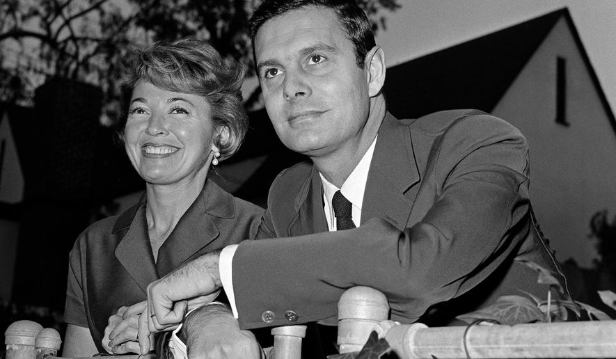 """FILE - In this Jan. 5, 1959 file photo, actor Louis Jourdan and his wife Berthe Fredrique pose at their home in Beverly Hills, Calif. Jourdan, the dashingly handsome Frenchman who starred in """"Gigi,"""" ''Can-Can,"""" ''Three Coins in the Fountain"""" and other American movies, has died on Saturday, Feb. 14, 2015. He was 93.  (AP Photo, File)"""