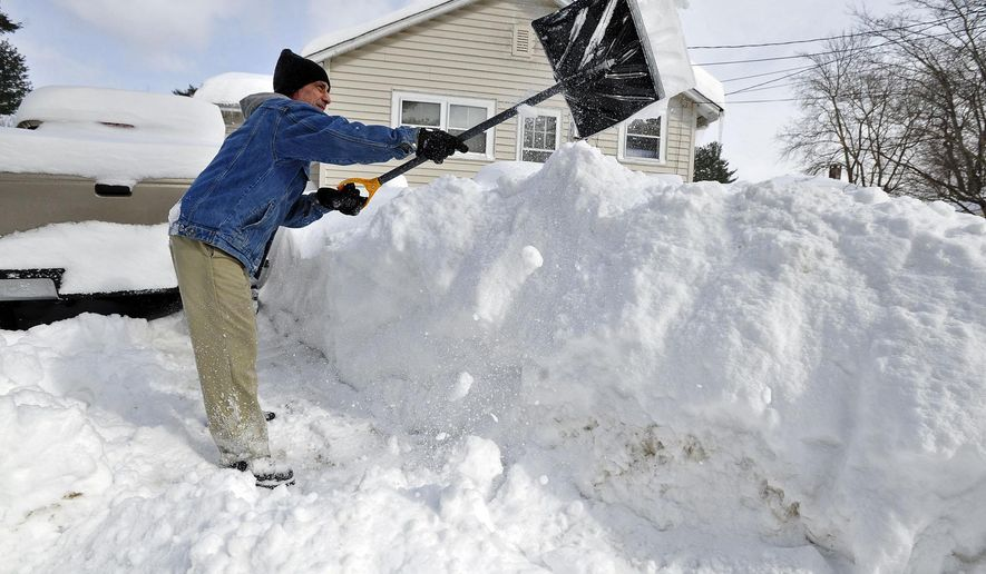 Allen Millette adds to the growing pile of snow in his yard in New Bedford, Mass., Sunday, Feb. 15, 2015. The National Weather Service is reporting snowfall over a foot across eastern Massachusetts, with pockets near 2 feet. (AP Photo/Standard Times, David W. Oliveira)