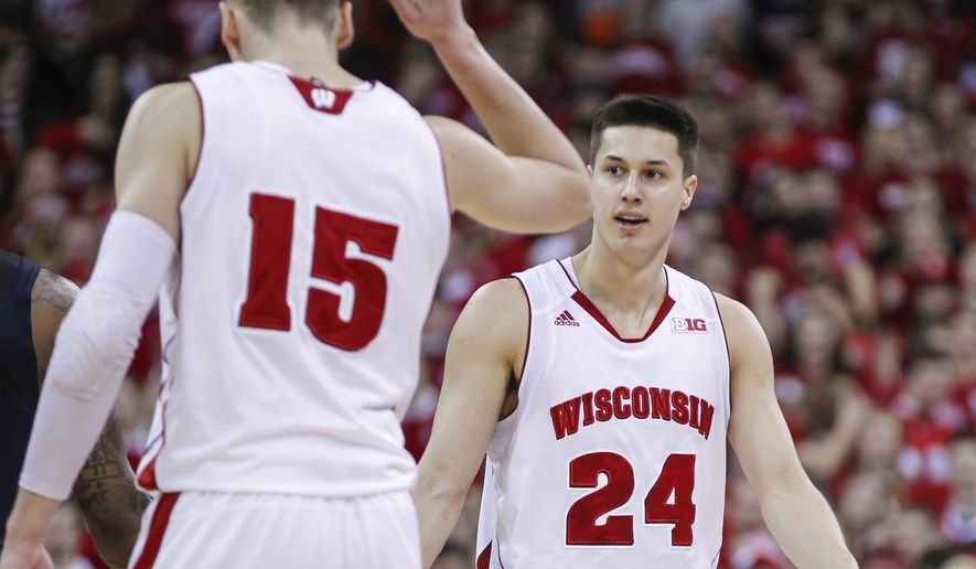 Wisconsin's Bronson Koenig (24) reacts with teammate Sam Dekker after hitting a 3-point basket during the second half of an NCAA college basketball game against Illinois, Sunday, Feb. 15, 2015, in Madison, Wis. Wisconsin won 68-49. (AP Photo/Andy Manis)