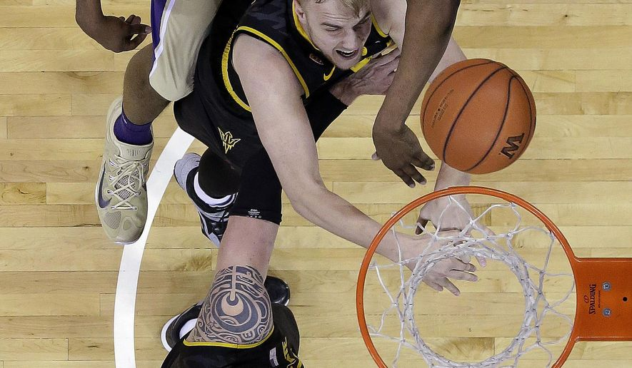 Washington's Shawn Kemp Jr., top reaches for a loose ball with Arizona State's Jonathan Gilling, center, and Eric Jacobsen in the first half of an NCAA college basketball game Sunday, Feb. 15, 2015, in Seattle. (AP Photo/Elaine Thompson)