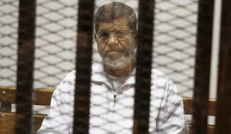 FILE - In this May 8, 2014 file photo, Egypt's ousted Islamist President Mohammed Morsi sits in a defendant cage in the Police Academy courthouse in Cairo, Egypt. A new trial for Morsi opened Sunday, Feb. 15, 2015, in Cairo, with prosecutors accusing him of espionage and leaking confidential information to Qatar while in office. Morsi, overthrown in July 2013 following mass protests demanding his resignation, does not recognize the court, and insists Egypt's current leadership came to power in a coup d'etat and is thus illegitimate. (AP Photo/Tarek el-Gabbas, File)