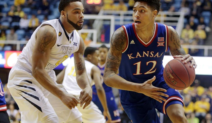 Kansas guard Kelly Oubre Jr. (12) looks to pass while being defended by West Virginia guard Jaysean Paige (0) during the first half of an NCAA college basketball game Monday, Feb. 16, 2015, in Morgantown, W.Va. (AP Photo/Raymond Thompson)