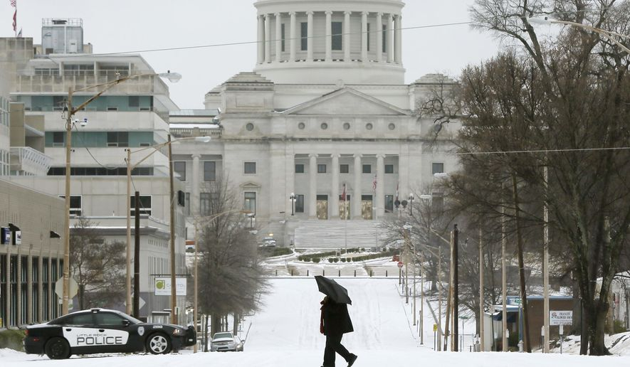 A woman walks across a street in Little Rock, Ark., Monday, Feb. 16, 2015. The National Weather Service issued a winter storm warning through Monday afternoon. (AP Photo/Danny Johnston)
