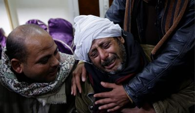 Mourners sought solace Monday outside the Virgin Mary Church in a village near Minya after militants affiliated with the Islamic State released an Internet video of the grisly killings of 21 Egyptian Coptic Christians who were captured in Libya. (Associated Press)