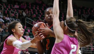 Maryland's Kiara Leslie center, goes for a contested shot between Michigan State's Aerial Powers, left, and Cara Miller, right, during the first half of an NCAA college basketball game, Monday, Feb. 16, 2015, in East Lansing, Mich. (AP Photo/Al Goldis)