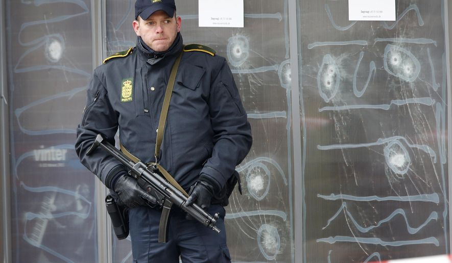 A police officer stands in front of the cultural center where an alleged shooter killed one person on Saturday in Copenhagen, Denmark, Monday, Feb. 16, 2015. The shooter was killed by police who believe he also shot a second person at a Jewish synagogue. (AP Photo/Michael Probst).