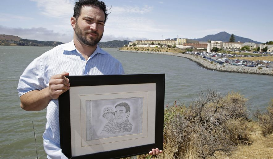In this Tuesday, July 8, 2014 photo, Dan Ager holds a graphite sketch showing his father, Alan Ager, and him, while standing outside San Quentin State Prison in San Quentin, Calif. Alan Ager was killed in 2010 at Salinas Valley State Prison and also served time in San Quentin. California state prison inmates are killed at a rate that is double the national average, and sex offenders like Alan Ager account for a disproportionate number of victims, according to an Associated Press analysis of corrections records. (AP Photo/Eric Risberg)