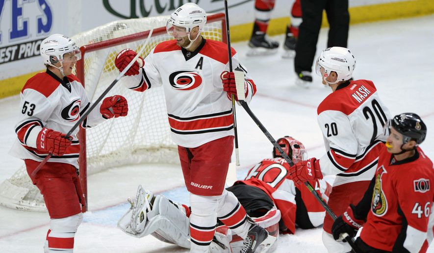 Ottawa Senators' goalie Robin Lehner lies on the ice as Carolina Hurricanes' Jeff Skinner, left, celebrates a second period goal with teammates Jordan Staal, center, and Riley Nash, right, during an NHL game in Ottawa, Ontario, Monday, Feb 16, 2015. (AP Photo/The Canadian Press, Sean Kilpatrick)