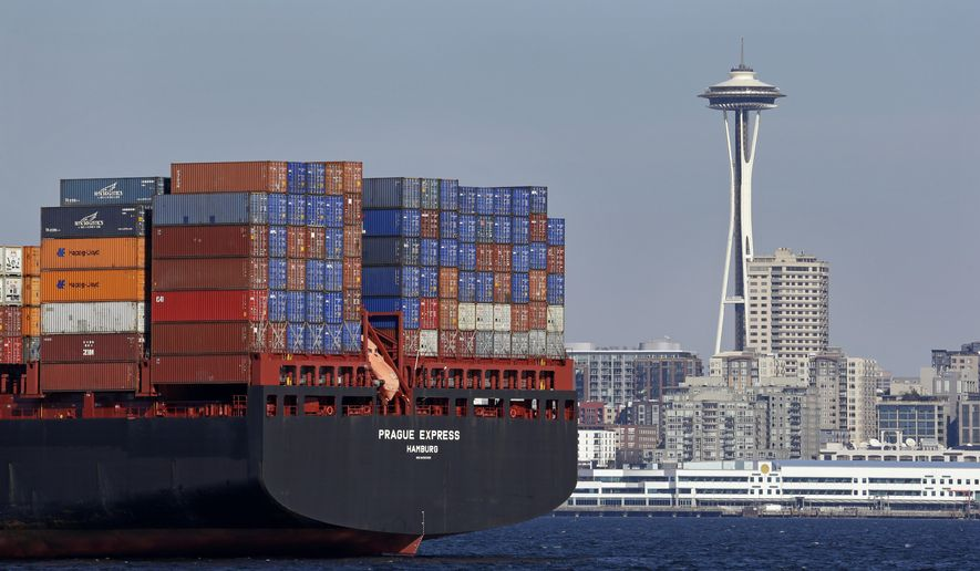 The Space Needle is seen just beyond a container ship anchored in Elliott Bay near downtown Sunday, Feb. 15, 2015, in Seattle. The waters off Los Angeles, Oakland and Washington state's Puget Sound have become parking lots for dozens of ships awaiting space at the docks. Employers are locking out dockworkers who man the cranes that lift cargo on and off ships, saying they have slowed work as a bargaining tactic, but the union denies that. (AP Photo/Elaine Thompson)
