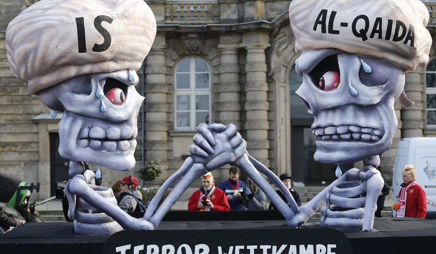 A carnival float depicts a writing 'terror competition' underneath skeletons with turbans and the writings IS and Al-Qaida during the traditional Rose Monday carnival parade in Duesseldorf, Germany, Monday, Feb. 16, 2015. The foolish street spectacles in the carnival centers of Duesseldorf, Mainz and Cologne, watched by hundreds of thousands of people, are the highlights in Germany's carnival season on Rose Monday. (AP Photo/Frank Augstein)