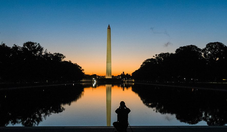 FILE- In this Oct. 8, 2014, file photo, a photographer is silhouetted in the reflecting pool as he captures the sunrise behind the Washington Monument in Washington. Government surveyors have determined a new height for the Washington Monument that's nearly 10 inches shorter than what has been thought for more than 130 years, officials will announce Monday, Feb. 16, 2015. (AP Photo/J. David Ake, File)