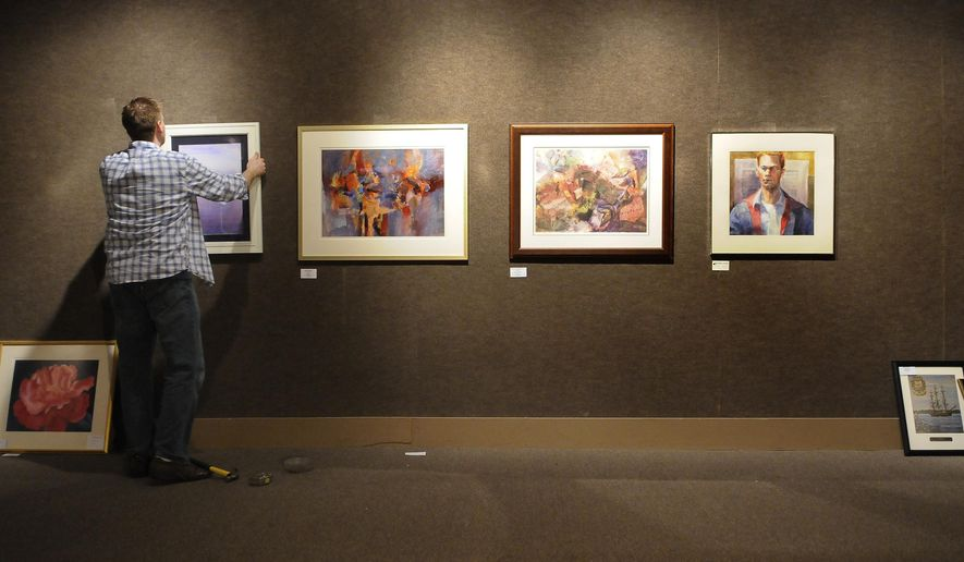 """In this Feb. 10, 2015 photo, Doug Bancroft, director of exhibits, hangs artwork for the Blue Water Art Association's """"Say It With Art: Fine Art & Whimsical Words"""" show on the walls, in the Port Huron Museum, in Port Huron, Mich. (AP Photo/The Port Huron Times Herald, Mark R. Rummel) NO SALES"""