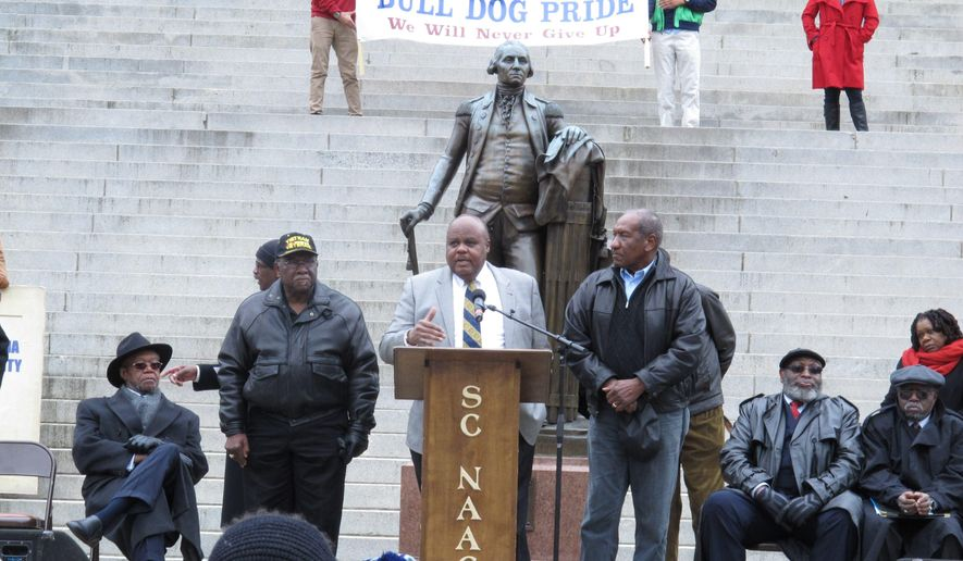 Rep. Joe Neal, center, tells a rally at the Statehouse that black lawmakers will not let South Carolina State University be shut down, on Monday, Feb. 16, 2015, in Columbia, S.C. Last week, a House panel passed a proposal to temporarily close SC State for a massive overhaul, then reopen it in 2017. Neal, Rep. Lonnie Hosey, left. and Rep. Bill Clyburn, right, are members of a House Ways and Means committee that will consider the proposal. (AP Photo/Jeffrey Collins)