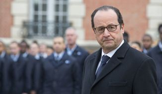 France's President Francois Hollande salutes the French flag as part of his visit to a public center for insertion of the Defense (EPIDE) in Montry, northeastern Monday, Feb. 16, 2015. (AP Photo/Jacques Brinon/Pool)