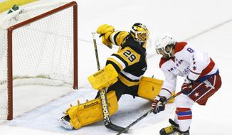 Washington Capitals' Alex Ovechkin (8) skates in on Pittsburgh Penguins goalie Marc-Andre Fleury (29) and scores in the first period of an NHL hockey game, Tuesday, Feb. 17, 2015, in Pittsburgh. (AP Photo/Keith Srakocic)