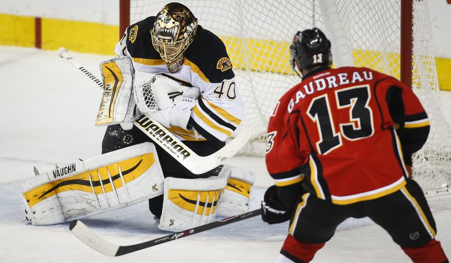 Boston Bruins goalie Tuukka Rask, left, from Finland, grabs a shot from Calgary Flames Johnny Gaudreau during second period NHL hockey action in Calgary, Alberta, Monday, Feb. 16, 2015. (AP Photo/The Canadian Press, Jeff McIntosh)