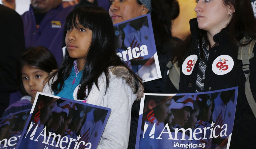 Nine-year-old Fatima Celedonia holds placard as she joins other immigration law reformers during a news conference in the Denver Public Library, Tuesday, Feb. 17, 2015, in Denver. (Associated Press) ** FILE **