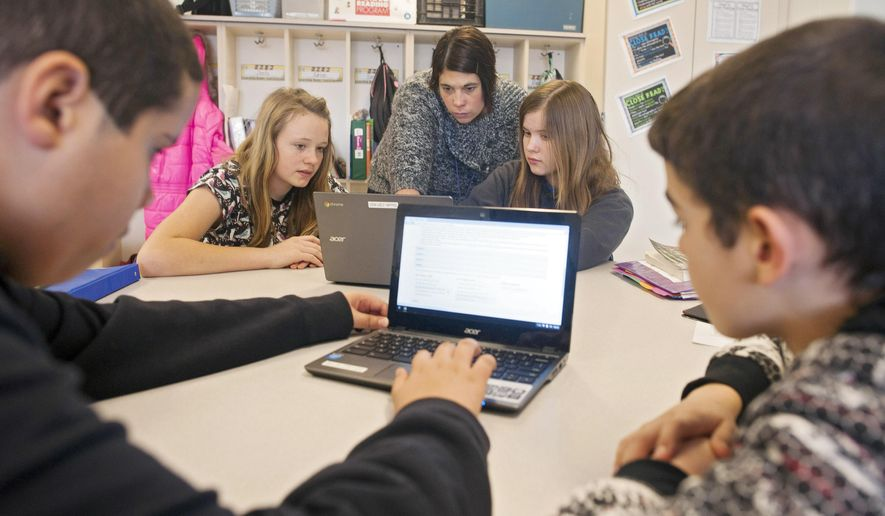 In this photo taken Feb. 12, 2015, sixth grade teacher Carrie Young, back center, answers questions from her students about an exercise on their laptops as they practice for the the Common Core State Standards Test in her classroom at Morgan Elementary School South in Stockport, Ohio. On Tuesday, Ohio becomes the first state to administer one of two tests in English language arts and math based on the Common Core standards developed by two separate groups of states. By the end of the year, about 12 million children in 28 states and the District of Columbia will take exams that are expected to be harder than traditional spring standardized state tests they replace. In some states, they'll require hours of additional testing time students will have to do more than just fill in the bubble. The goal is to test students on critical thinking skills, requiring them to describe their reasoning and solve problems. (AP Photo/Ty Wright)