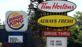 FILE - This Aug. 25, 2014 file photo shows signs for Burger King and Tim Hortons locations in Ottawa, Ontario. Burger King and Tim Hortons owner Restaurant Brands International Inc. reports quarterly financial results before the market opens Tuesday, Feb. 17, 2015. (AP Photo/The Canadian Press, Sean Kilpatrick, File)
