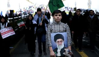 An Iranian man holds a portrait of Supreme Leader Ayatollah Ali Khamenei during a rally commemorating the 36th anniversary of Islamic Revolution under Azadi Tower, Tehran, Iran, Wednesday, Feb. 11, 2015. Iran marked the anniversary of its 1979 Islamic Revolution on Wednesday with massive rallies, with many chanting against the U.S. and Israel as the country tries to reach a permanent deal with world powers over its contested nuclear program. (AP Photo/Ebrahim Noroozi)