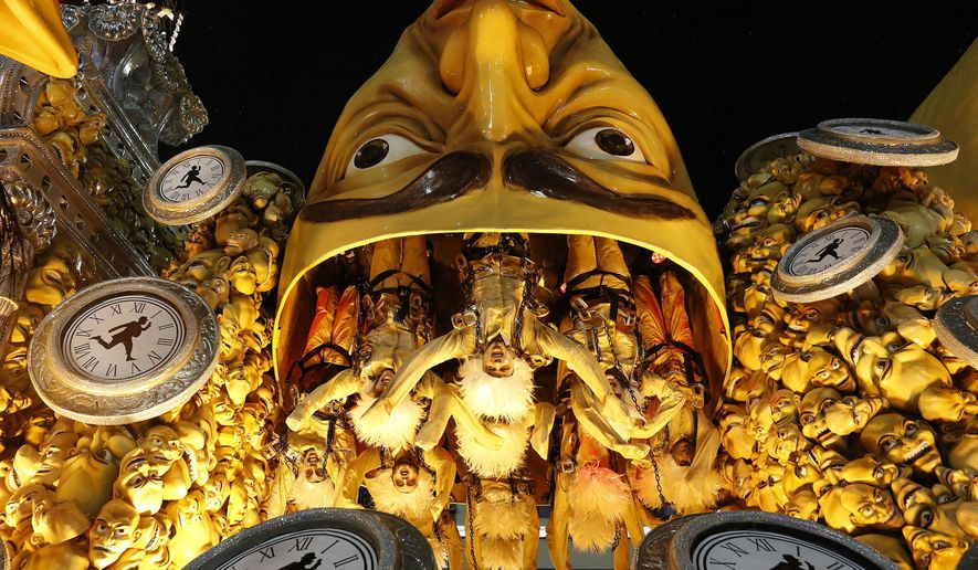 Performers from the Mocidade samba school hang upside down from their float, during the Carnival parade at the Sambadrome in Rio de Janeiro, Brazil, Monday, Feb. 16, 2015. (AP Photo/Leo Correa)