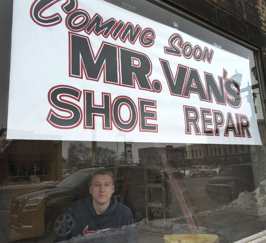 Garrett Williams, 21, sits in the window of the new Mr. Van's Shoe Repair in Old Town Saginaw, Feb. 11, 2015. The original Mr Van's in Saginaw Township's Green Acres Plaza closed last year and Williams purchased the business. Williams and a construction crew are renovating the building on Court exposing and cleaning the original floor and brick walls with plans to open on April 1.   (AP Photo/The Saginaw News, Jeff Schrier) ALL LOCAL TELEVISION OUT; LOCAL TELEVISION INTERNET OUT