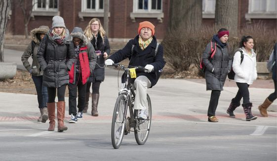 In this Feb. 16, 2015 photo University of Illinois students cross Fourth Street on campus in Champaign, Ill. Monday Feb. 16, 2015. A school spokeswoman says the University of Illinois at Urbana-Champaign has increased the number of in-state residents being accepted for fall 2015. (AP Photo/The News-Gazette, Rick Danzl) **FILE**