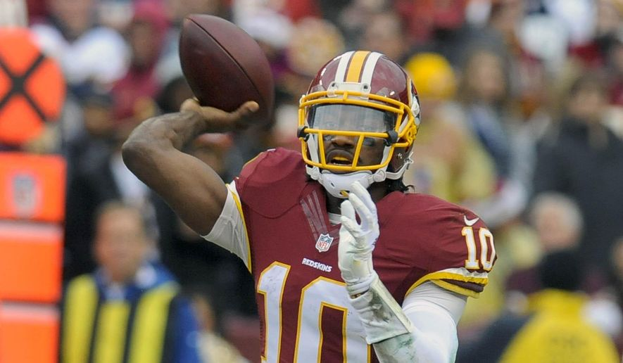 FILE - In this Sunday, Dec. 28, 2014 file photo, Washington Redskins quarterback Robert Griffin III (10) passes the ball during the first half of an NFL football game against the Dallas Cowboys in Landover, Md. Former Redskins head coach Mike Shanahan says things went downhill for him in Washington because Robert Griffin III and team owner Dan Snyder both wanted the quarterback to become a dropback passer, Wednesday, Feb. 18, 2015. (AP Photo/Richard Lipski, File)