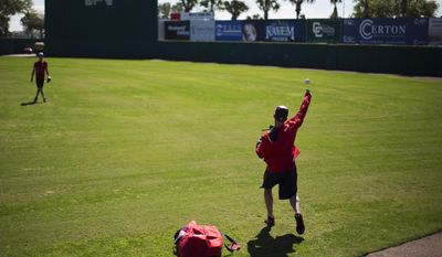 Washington Nationals bullpen catcher Octavio Martinez, right, throws the ball to pitcher Doug Fister during an informal spring training baseball workout, Wednesday, Feb. 18, 2015, in Viera, Fla. (AP Photo/David Goldman)