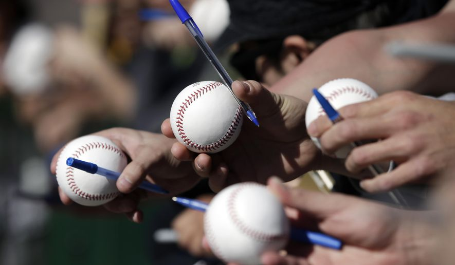 San Francisco Giants fans holds baseballs and pens in hopes for getting an autograph as players arrive for spring training baseball workouts Wednesday, Feb. 18, 2015, in Scottsdale, Ariz. Giants pitchers and catchers have their first official workout scheduled for Thursday. (AP Photo/Darron Cummings)
