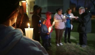 In this Feb. 17, 2015 photo, a group lights candles at a rally for immigration reform in front of Devine Redeemer Presbyterian Church sponsored by the Texas Organizing Project in San Antonio, Texas. Immigrants across the country expressed disappointment Tuesday after a federal judge put a hold on President Barack Obama's plan to protect more than 4 million people living illegally in the U.S. from deportation. But many said they haven't lost hope. (AP Photo/The San Antonio Express-News, Bob Owen)