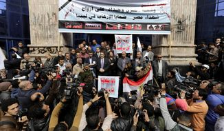 "Egyptian journalists hold a protest for Christians who were killed in Libya, at the journalists syndicate in Cairo, Egypt, Wednesday, Feb. 18, 2015. An Islamic State video released on 15 February claimed to show the extremist group beheading 21 Egyptian Christians abducted in Libya more than a month ago. Arabic on the banners read, ""a protest to morn the victims of terrorism in Libya,"" top, "" we are not afraid from ISIS terrorism,"" center. (AP Photo/Amr Nabil)"