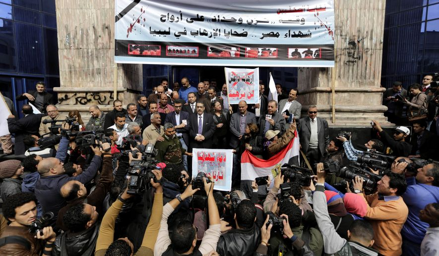 """Egyptian journalists hold a protest for Christians who were killed in Libya, at the journalists syndicate in Cairo, Egypt, Wednesday, Feb. 18, 2015. An Islamic State video released on 15 February claimed to show the extremist group beheading 21 Egyptian Christians abducted in Libya more than a month ago. Arabic on the banners read, """"a protest to morn the victims of terrorism in Libya,"""" top, """" we are not afraid from ISIS terrorism,"""" center. (AP Photo/Amr Nabil)"""