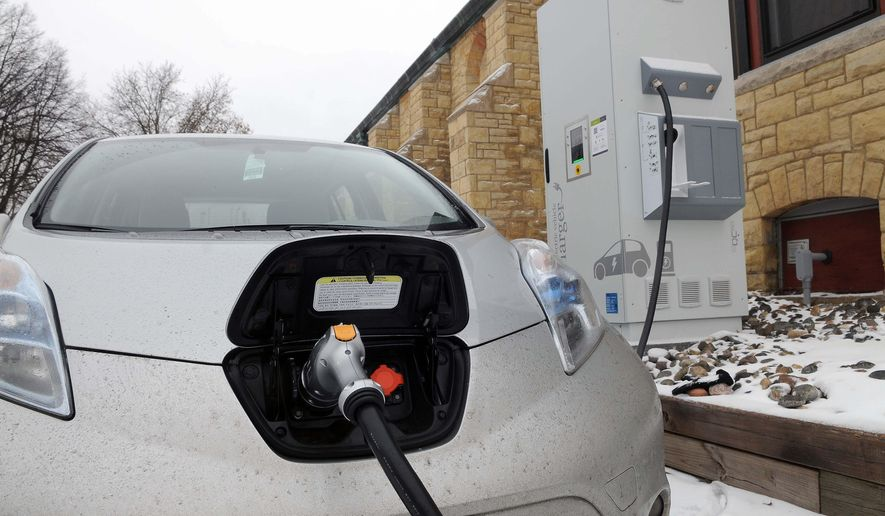 ADVANCED FOR RELEASE MONDAY, FEBRUARY 23, 2015 Dale Howey's Nissan Leaf electric car charges quickly using the fast charger in the parking lot of the Unitarian Universalist Church  in St. Paul,  on Tuesday, Feb. 10, 2015. (AP Photo/St. Paul Pioneer Press, Scott Takushi)