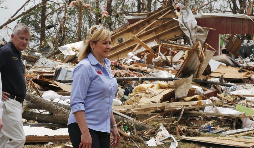 FILE - In this May 20, 2013 file photo, John Doak, left, Oklahoma insurance commissioner, walks with Oklahoma Gov. Mary Fallin, right, through tornado damage near Shawnee, Okla. About 1,000 emergency managers, insurance company representatives and city leaders from across the country are expected next week at the National Tornado Summit in Oklahoma. (AP Photo Sue Ogrocki, File)