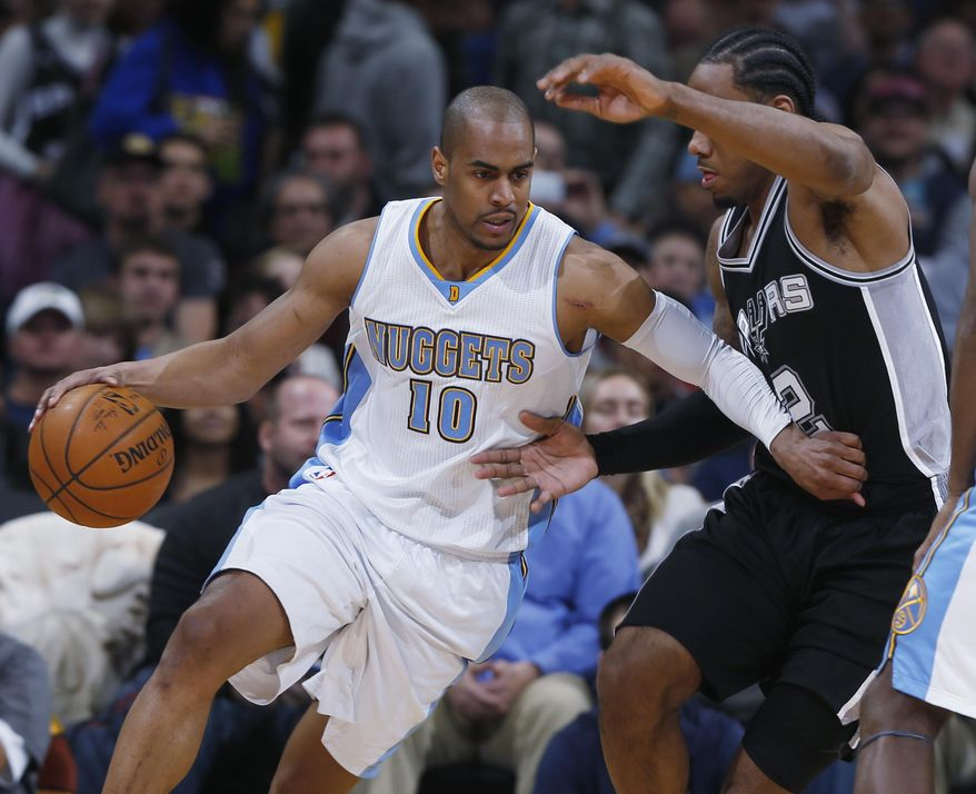 In this photograph taken on Tuesday, Jan. 20, 2015, Denver Nuggets guard Arron Afflalo, left, works the ball inside for a shot as San Antonio Spurs forward Kawhi Leonard covers in the third quarter of an NBA basketball game in Denver. Afflalo was traded along with teammate Alonzo Gee to the Portland Trail Blazers for three players on Thursday, Feb. 19, 2015, before the NBA trading deadline. (AP Photo/David Zalubowski)