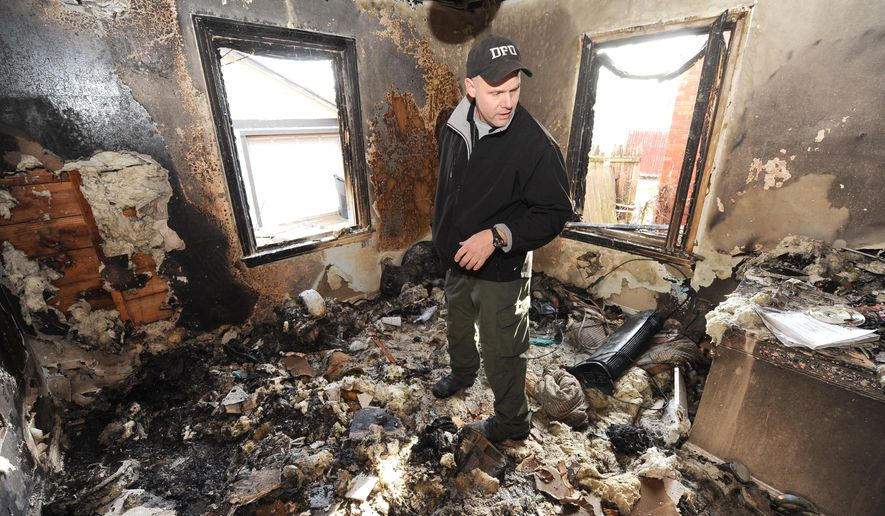 In this photo taken on Dec. 4, 2014, Lt. Joseph Crandall, Arson Investigator, Detroit Fire Department, examines a suspicious fire at 19662 Westphalia Street in Detroit. A published report describes arson is a raging epidemic in Detroit, where buildings burn faster than the city can demolish them. The Detroit News, citing city records that it analyzed, reports that last year Detroit had 3,839 suspicious fires and demolished 3,500 buildings.  (AP Photo/Detroit News, Max Ortiz)  DETROIT FREE PRESS OUT; HUFFINGTON POST OUT