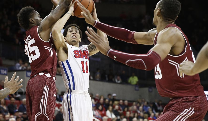 SMU's Nic Moore (11) looks to shoot in front of Temple's Quenton DeCosey (25) and Devontae Watson, right, during the first half of an NCAA basketball game, Thursday, Feb. 19, 2015, in Dallas. (AP Photo/Jim Cowsert)