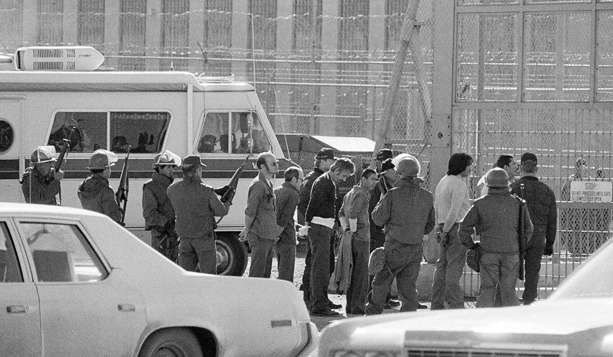 FILE - This Feb. 5, 1980 file photo shows inmates guarded at the back gate of the New Mexico State Penitentiary by National Guard in Santa Fe, N.M., following a prison riot. More than a dozen guards were held hostage during one of the nation's deadliest prison riots 35 years ago. Now, one lawmaker wants to compensate the guards who were diagnosed with post-traumatic stress disorder as a result. (AP Photo/Ed Andrieski, File)
