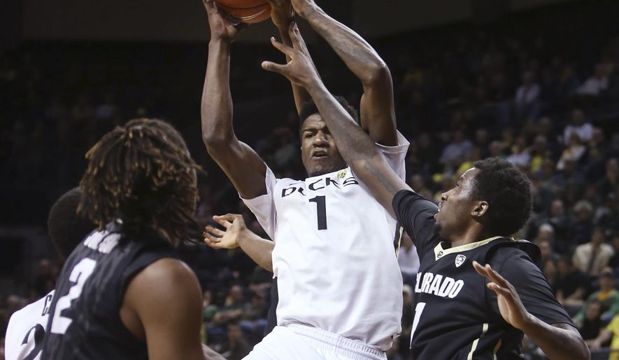 Oregon's Jordan Bell, center, vies for a rebound between Colorado's Xavier Talton, left, and Wesley Gordon, right, during the first half of an NCAA college basketball game in Eugene, Ore., Wednesday, Feb. 18, 2015. (AP Photo/Chris Pietsch)