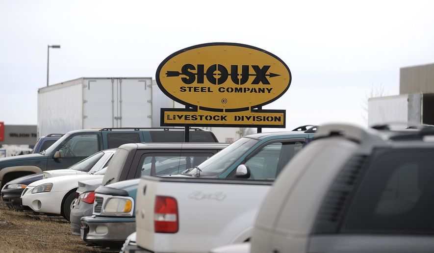 In this photo taken on Thursday, Feb. 12, 2015, cars are parked near a sign for Sioux Steel in Lennox, S.D.  Employees at Sioux Steel in Lennox are gradually getting back to work, after a shooting incident a week ago that killed one worker and injured two others. The company reopened Monday, Feb. 16, 2015, and has been letting employees come back to work whenever they feel ready, CEO Scott Rysdon told the Argus Leader newspaper. Sioux Steel also is offering counseling and other assistance to workers who want it.  (AP Photo/Argus Leader, Emily Spartz-Weerheim) NO SALES
