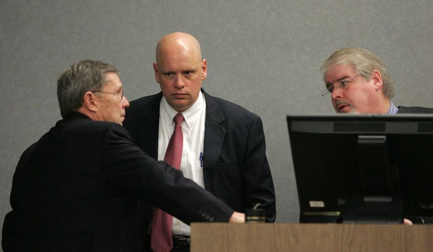 Prosecutor Michael Jacobsen, center, and defense attorney Steven Addington, left, confer with Judge Terry Rickers, Thursday, Feb. 19, 2015, in Waterloo, Iowa. Attorneys have delivered closing arguments and jurors have entered deliberation in the trial of an Iowa woman accused of killing her husband and his girlfriend more than 30 years ago. (AP Photo/Waterloo Courier, Dennis Magee)