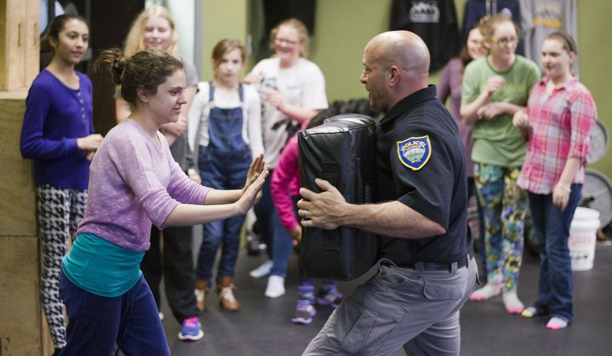 Jackson Police Department dectective Greg Adam works with Sarah Sampson, 13, during a self-defense training class Wednesday, Jan. 28, 2015, at Gym 22 in Jackson, Wyo. The class teaches girls in their early teens basic self-defense techniques. (AP Photo / Jackson Hole News&Guide, Bradly J. Boner)