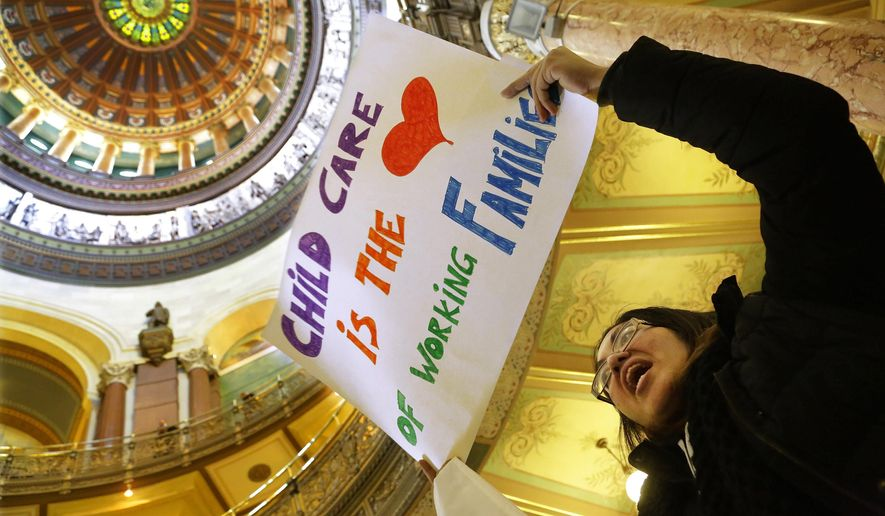 Erica Hurtado of Chicago, participates in a rally to save Illinois child care programs for children and working families in the rotunda at the Illinois State Capitol Thursday, Feb. 19, 2015, in Springfield, Ill.   Gov. Bruce Rauner may have proposed a budget that includes no new taxes, but any Illinois resident who thinks they've dodged an increase may want to wait a bit. Democrats say they'll continue to push for a hike, either in Illinois' income tax or other sources, to avoid some of the huge cuts the GOP governor proposed. (AP Photo/Seth Perlman)