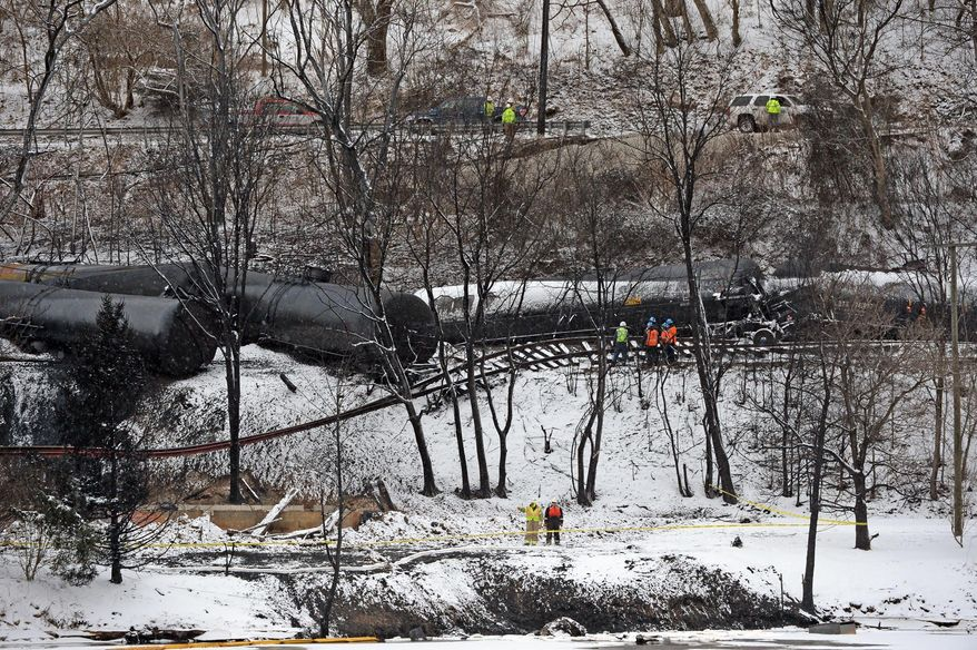 Workers clear tracks around the train derailment in Mount Carbon, W.Va., Thursday, Feb. 19, 2015. The derailment shot fireballs into the sky, leaked oil into a Kanawha River tributary, burned down a house nearby and forced nearby water treatment plans to temporarily shut down. CSX will begin transferring oil from damaged cars to other tanks for removal from the site when conditions become safe.  (AP Photo/Charleston Daily Mail, Tom Hindman)