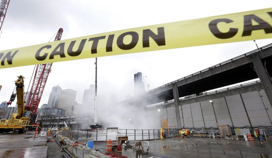 """Caution"" tape to keep visitors back is afixed near a cloud of concrete dust mixed with steam above an access pit for a damaged digging machine for the highway 99 tunnel project Thursday, Feb. 19, 2015, in Seattle. The cutterhead on Seattle's troubled tunnel machine broke through the 20-foot-thick wall of a rescue pit earlier Thursday. (AP Photo/Elaine Thompson)"