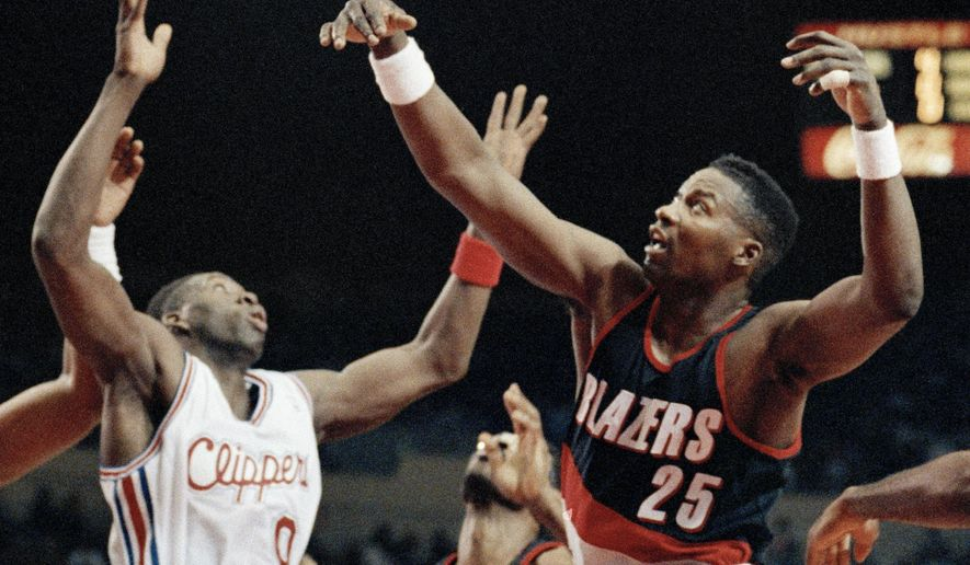 FILE - In this Feb. 21, 1992, file photo, Los Angeles Clippers' Doc Rivers, left, fights Portland Trail Blazers' Jerome Kersey for a rebound during an NBA basketball game in Los Angeles. Kersey, the small forward who played his first 11 NBA seasons with the Trail Blazers and helped the San Antonio Spurs win the 1999 title, has died. He was 52. The Trail Blazers confirmed Wednesday night, Feb. 18, 2015, that Kersey had died, but didn't provide details. (AP Photo/Craig Fuji, File)