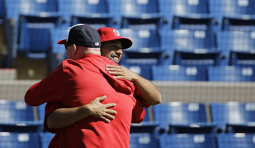 Washington Nationals pitcher Gio Gonzalez, right, embraces manager Matt Williams while crossing paths doing media interviews as pitchers and catchers officially report for spring training baseball, Thursday, Feb. 19, 2015, in Viera, Fla. (AP Photo/David Goldman)