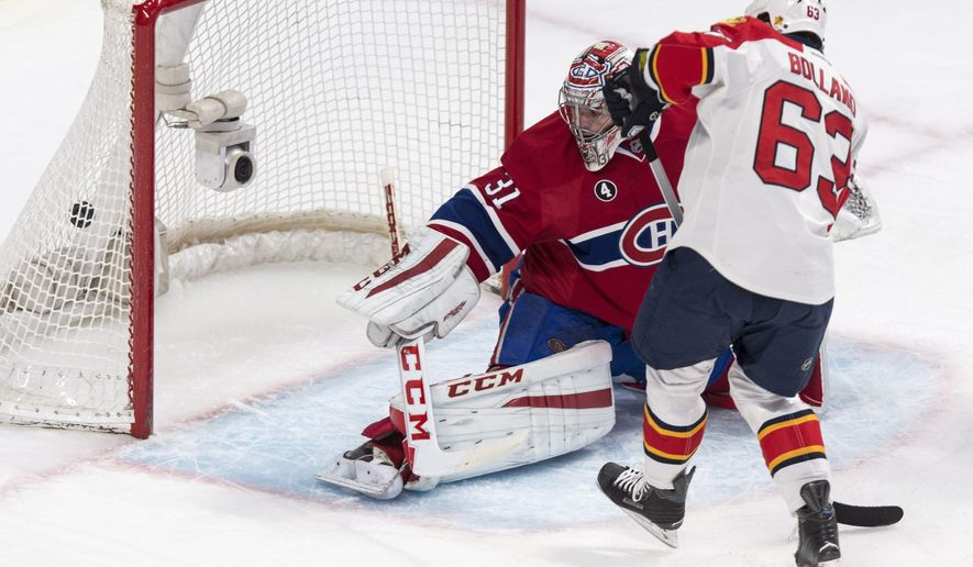 Montreal Canadiens goalie Carey Price and Florida Panthers' Dave Bolland watch the puck go into the net on a goal by Panthers' Tomas Fleischmann during the second period of an NHL hockey game Thursday, Feb. 19, 2015, in Montreal. (AP Photo/The Canadian Press, Paul Chiasson)