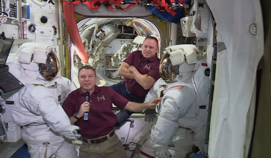 In this image from video made available by NASA, astronauts Terry Virts, left, and Barry Wilmore speak next to their spacesuits during an interview aboard the International Space Station on Wednesday, Feb. 18, 2015. A series of upcoming spacewalks will begin a day late. The first spacewalk by the two U.S. crew members was supposed to occur Friday, 20, 2015. But a day ahead of the maneuver, NASA bumped it to Saturday to complete a spacesuit investigation. (AP Photo/NASA)